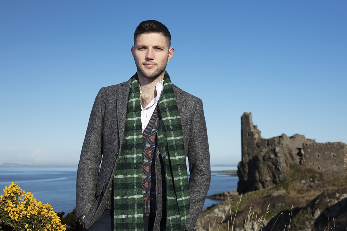 Musician Colm Keegan wearing the Rosemarkie waistcoat and a woven scarf by Alice Starmore